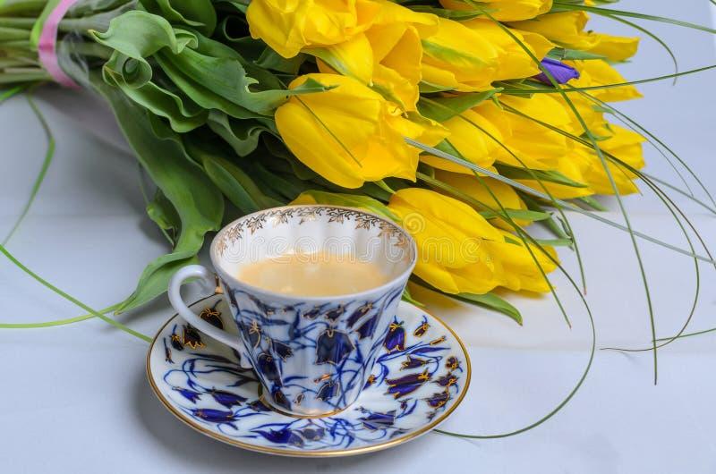 Свежие желтые тюльпаны и чашка кофе стоковое фото rf