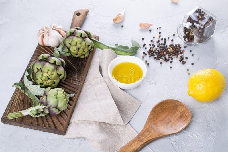 Свежие зеленые артишоки на разделочной доске готовой для того чтобы сварить и ингридиентах чесноке, лимоне и оливковом масле стоковое изображение