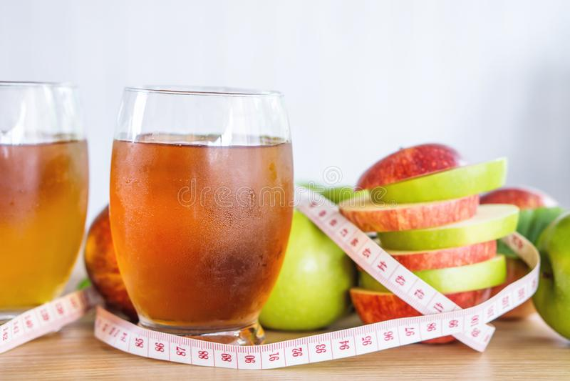 Свежие зеленые и красные стекла куска и сока яблока с измеряя лентой стоковое изображение