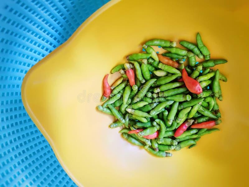 Свежие зеленые и красные Chilies в желтом шаре над голубой пластиковой корзиной стоковое фото rf