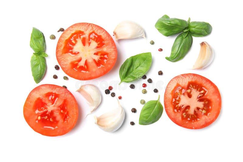 Свежие зеленые листья, томаты и чеснок базилика на белой предпосылке стоковое изображение rf