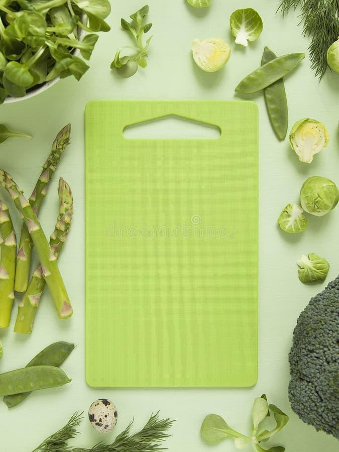 Свежие зеленые яичка овощей, трав, салата и триперсток с яркой разделочной доской в середине стоковая фотография rf