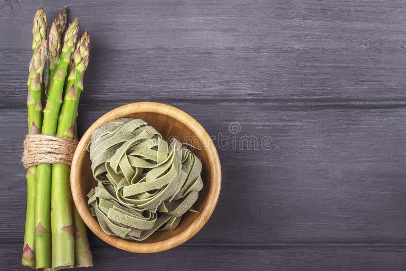 Свежие зеленые макаронные изделия спаржи и fettuccine итальянские в шаре на wo стоковое изображение