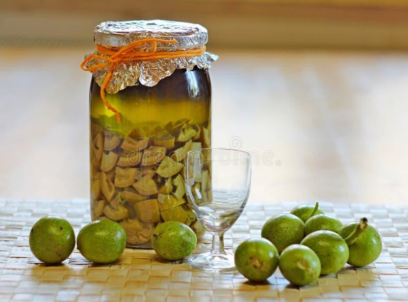 Свежие зеленые, молодые грецкие орехи и бутылка домодельной настойки принятые как выход для болей в животе стоковые изображения