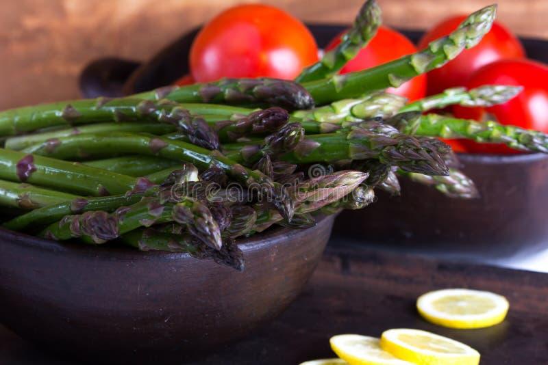 Свежие зеленые спаржа и томаты стоковые фотографии rf