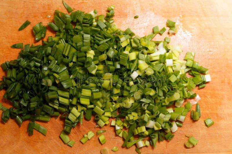 Свежие зеленые луки на разделочной доске стоковая фотография rf