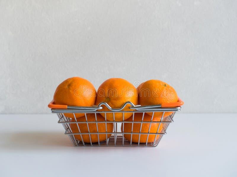 Свежие зрелые апельсины мандарина плод или tangerines в небольшой корзине еды металла на серой предпосылке стоковые изображения rf