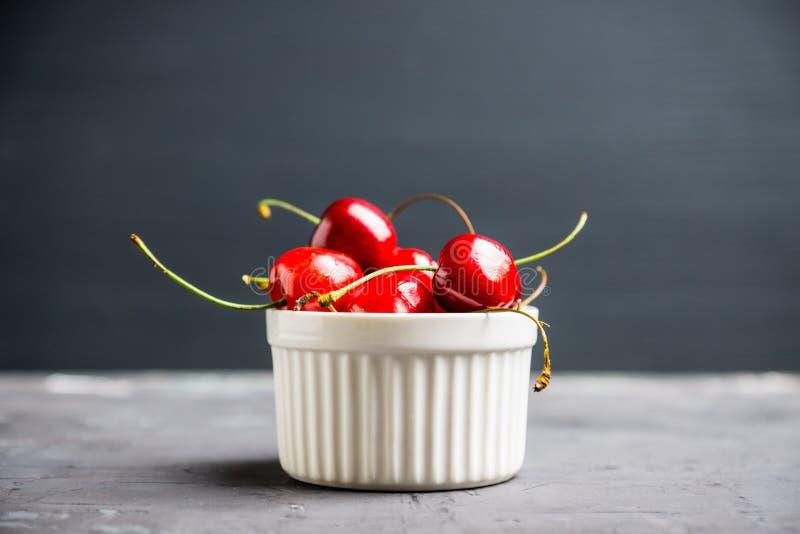 Свежие зрелые вишни в малом белом керамическом шаре на деревенской предпосылке стоковое фото rf