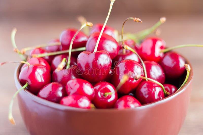 Свежие зрелые вишни в плите на деревянном столе стоковое фото