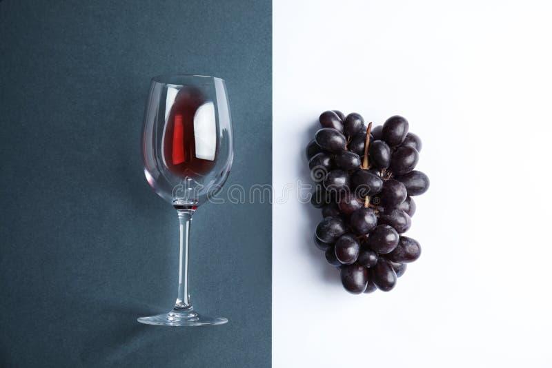 Свежие зрелые сочные виноградины и стекло с красным вином на предпосылке цвета стоковые изображения rf