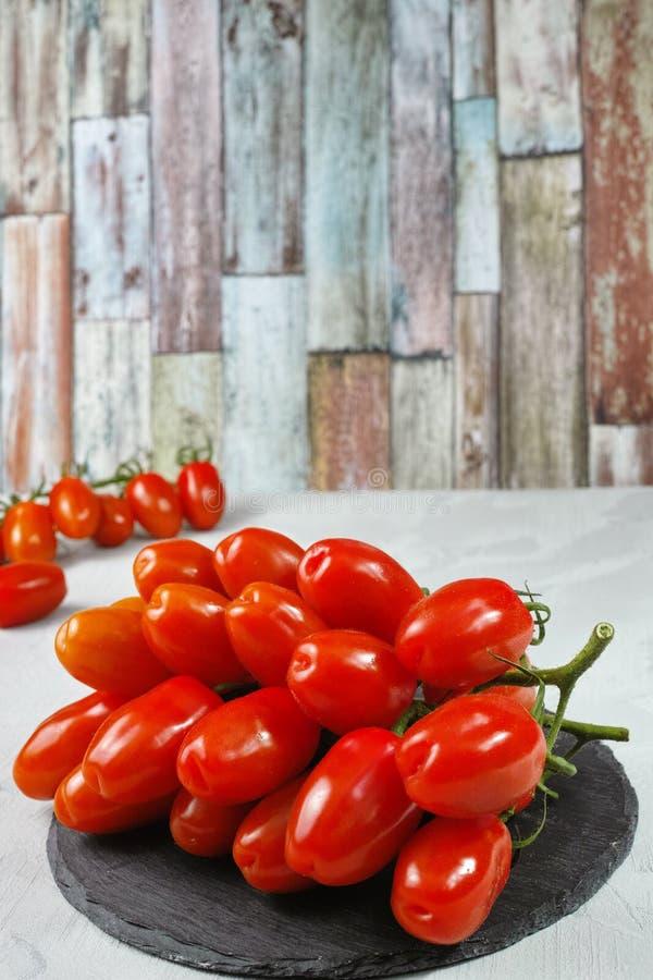 Свежие зрелые мини томаты roma на серой доске стоковые фото