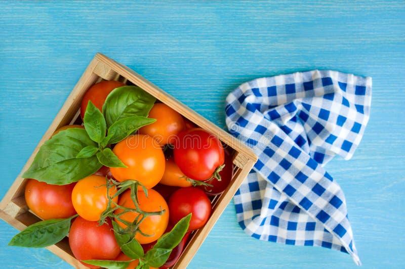 Свежие зрелые томаты и базилик в коробке на голубой предпосылке Красные и желтые томаты стоковая фотография