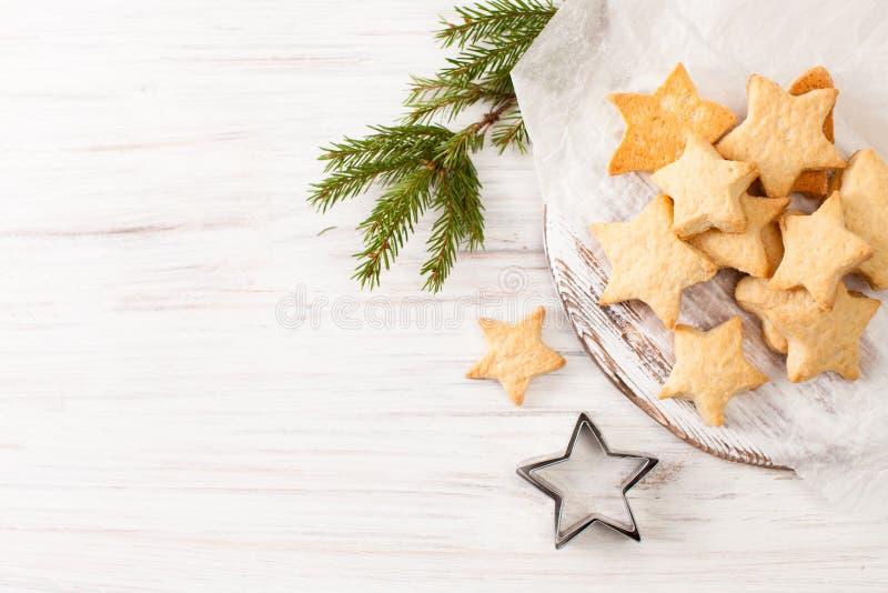 Свежие испеченные печенья на бумаге выпечки с елью разветвляют на белизне стоковое фото