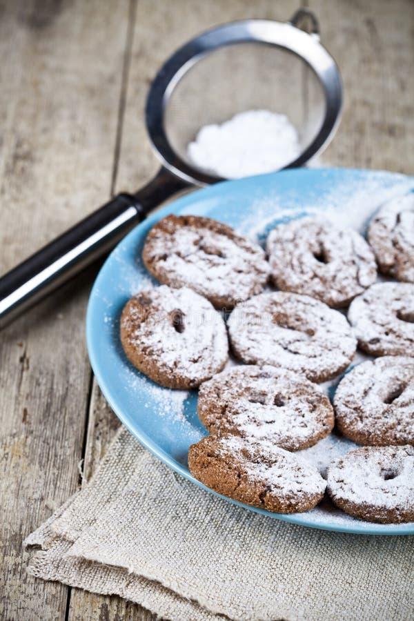 Свежие испеченные печенья обломока шоколада с порошком сахара на голубом крупном плане стрейнера плиты и металла на деревенском д стоковое изображение rf