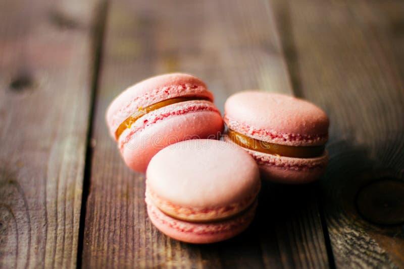 Свежие испеченные фиолетовые розовые macarons печений печенья macaroon, макарон в дисплее магазина розничной торговли, конце ввер стоковое изображение rf