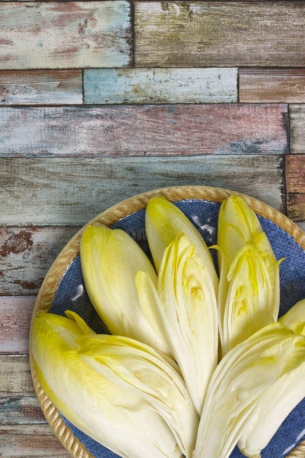Свежие листья салата цикория помещенные на голубой плите стоковые изображения rf