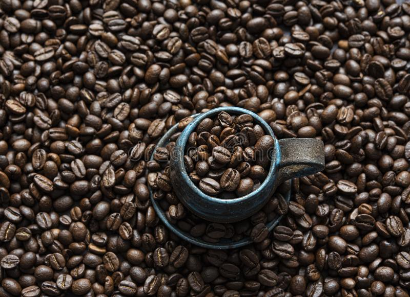 Свежие кофейные зерна ароматности на голубой предпосылке взгляда сверху чашки стоковые изображения rf