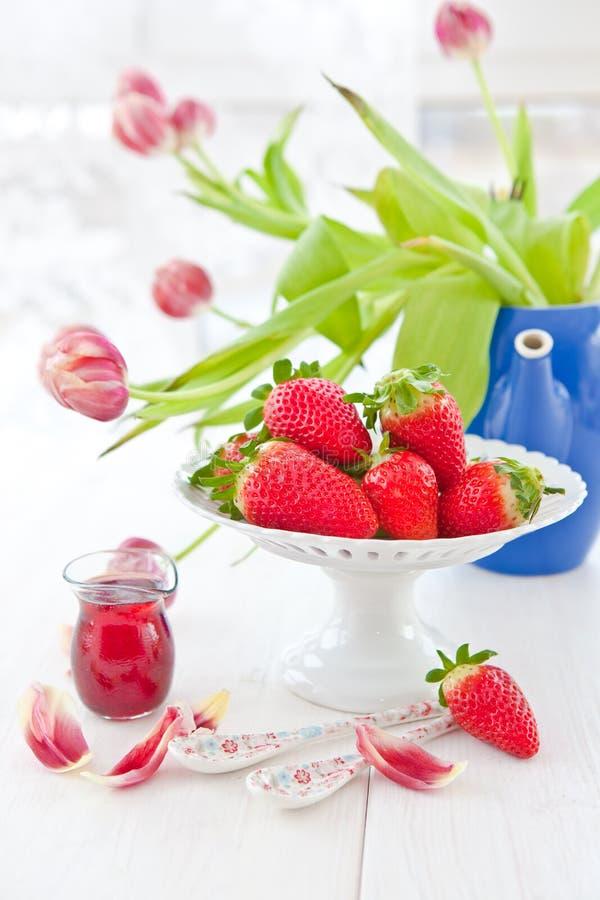 Свежие красные клубники и тюльпаны стоковая фотография rf