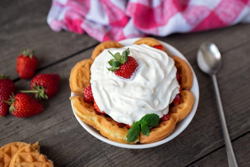 Свежие красные клубники и взбитая сливк на waffle стоковые изображения
