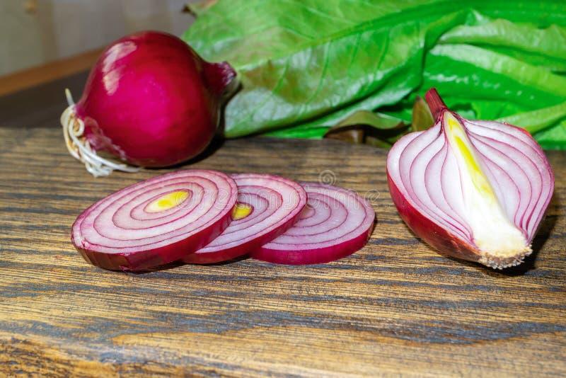 Свежие красные луки и листья салата на очень старой деревенской деревянной разделочной доске стоковое фото