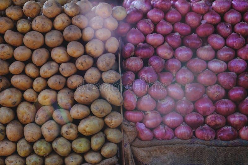Свежие красные луки и potatos лежа в строках на vegetable рынке стоковая фотография rf