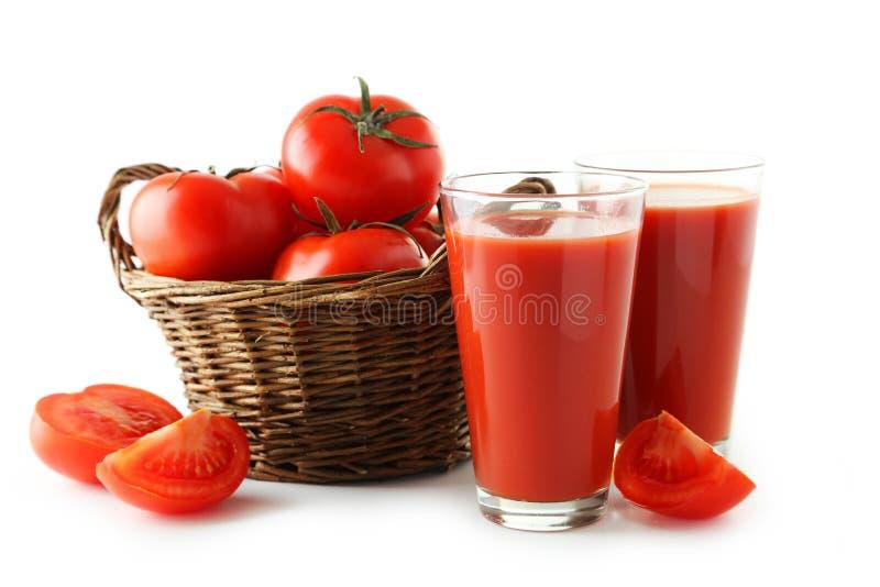 Свежие красные томаты в соке корзины и томата в стекле изолированном на белизне стоковое фото rf
