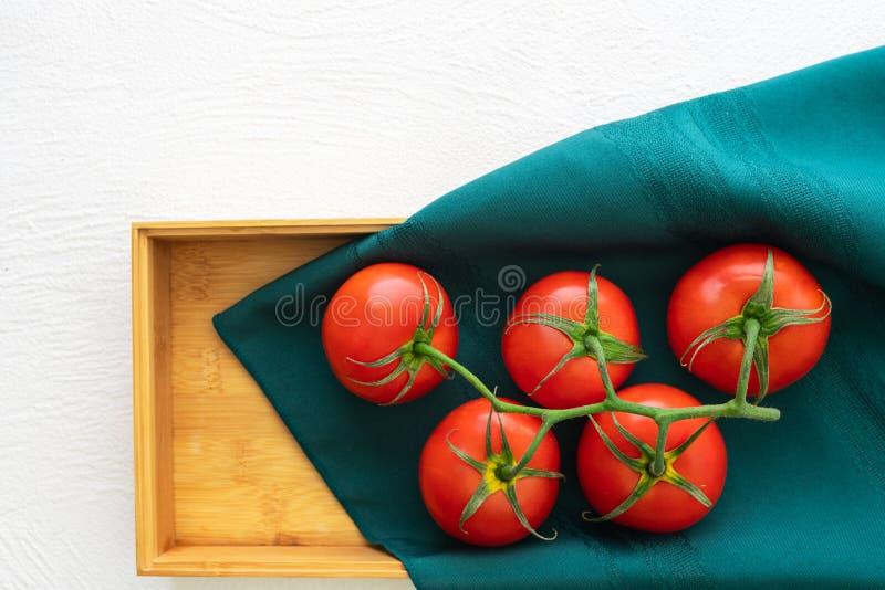 Свежие красные томаты, деревянный контейнер, белая предпосылка, конец вверх, взгляд сверху стоковое изображение