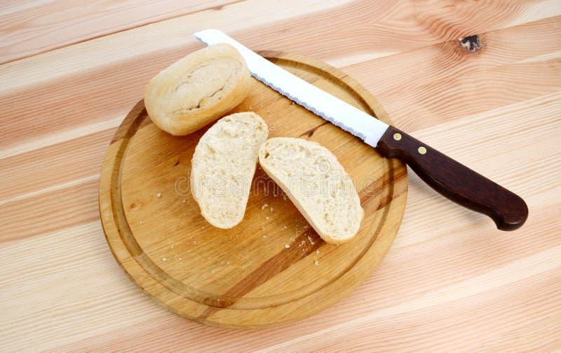 Свежие крены, весь и уменьшанный вдвое, с ножом хлеба стоковая фотография rf