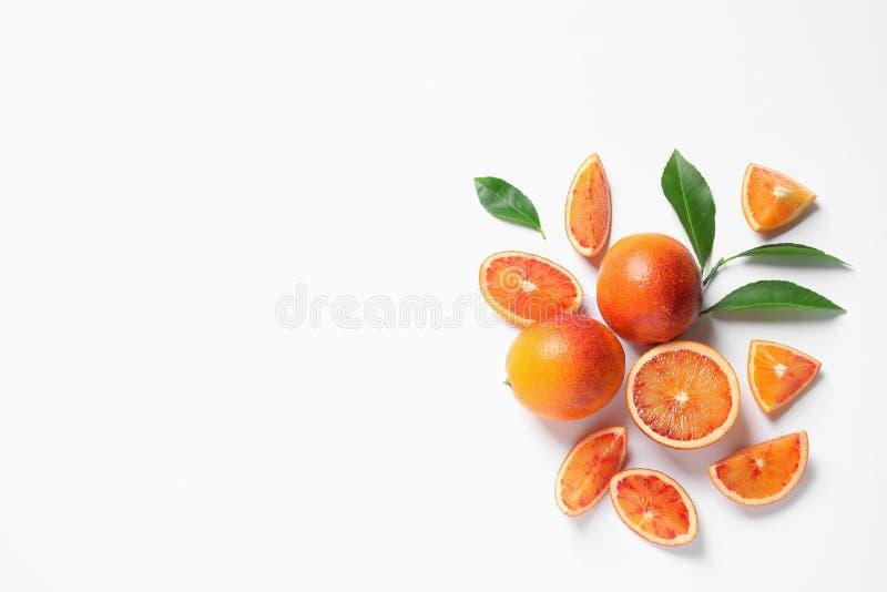 Свежие кровопролитные апельсины и листья на белой предпосылке, взгляде сверху стоковые изображения rf