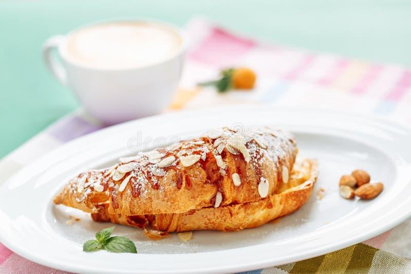 Свежие круассаны покрытые с вареньем и отрезанной миндалиной на запачканной предпосылке чашки coffe на завтрак стоковые изображения