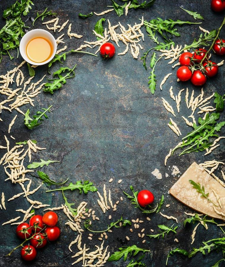 Свежие макаронные изделия с маслом, томатами и ингридиентами для варить на деревенской предпосылке, взгляд сверху стоковое фото