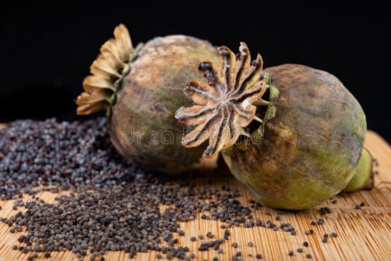 Свежие маковые семенена полили на деревянной доске кухни Различные маковые семенена подготовленные для печениь кухни стоковая фотография