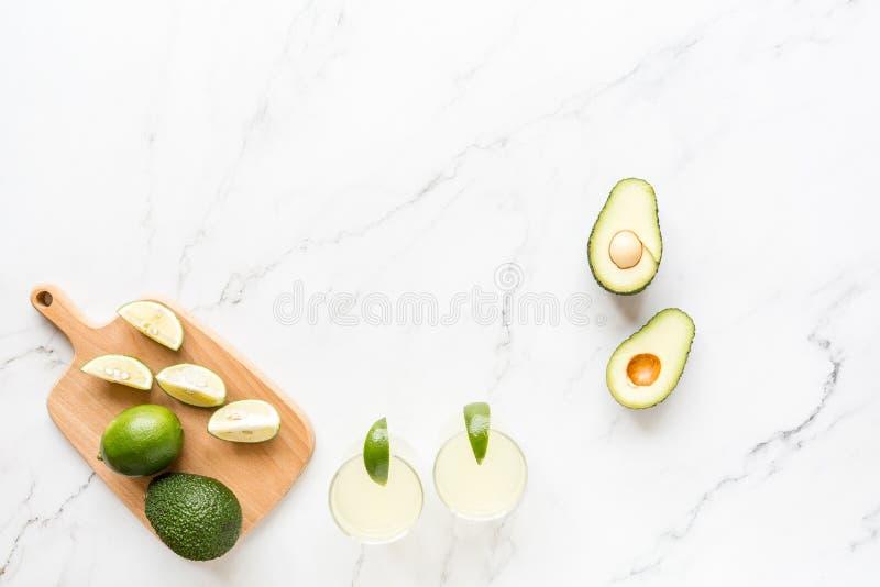 Свежие обломоки авокадоа, известки, напитка и nacho лежа на мраморной предпосылке Рецепт для партии Cinco de Mayo Взгляд сверху,  стоковое фото