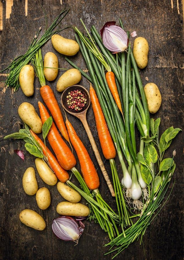Свежие овощи и ингридиенты трав для варить с старой ложкой на темной деревенской деревянной предпосылке стоковая фотография