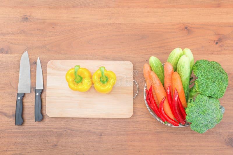 Свежие овощи и нож на разделочной доске на деревянной таблице стоковое изображение