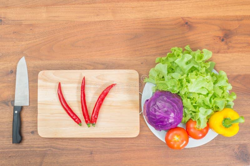 Свежие овощи и нож на разделочной доске на деревянной таблице стоковые фотографии rf