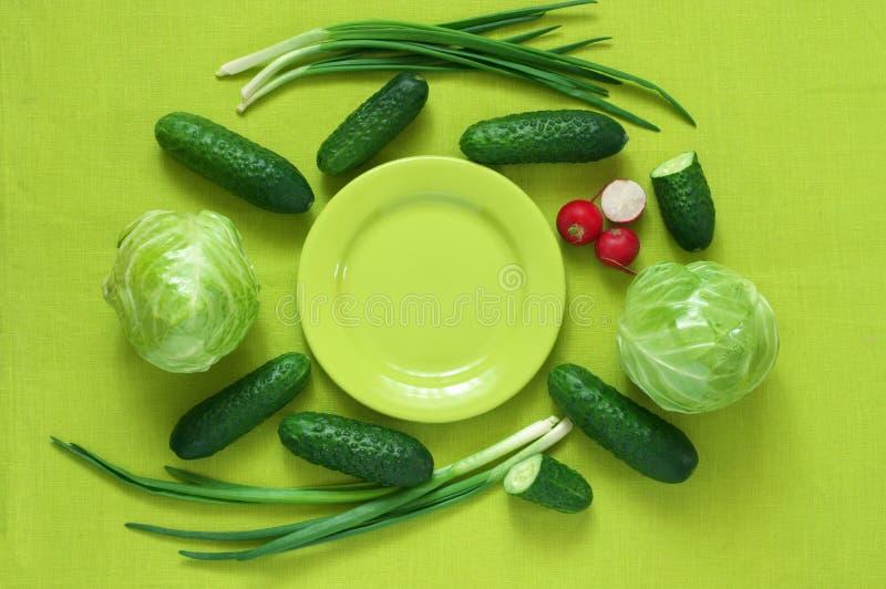 Свежие овощи и плита на зеленом цвете стоковое изображение rf