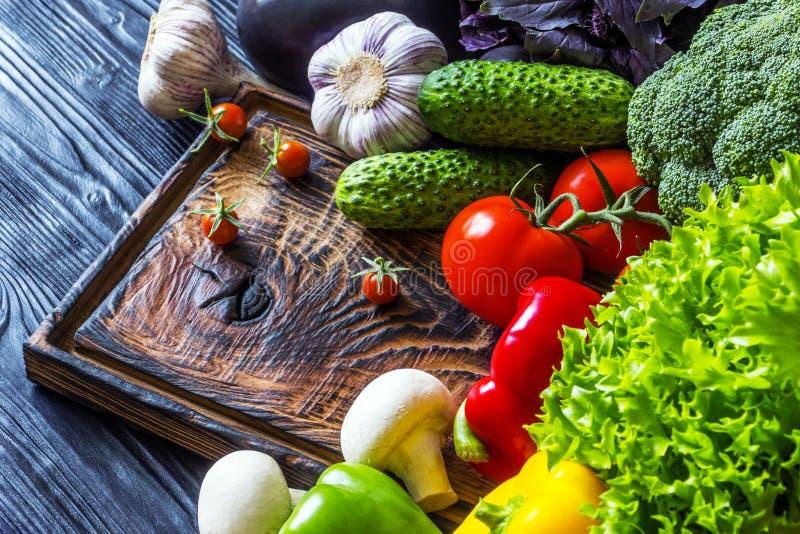 Свежие овощи лежа на старой деревянной доске стоковое изображение rf