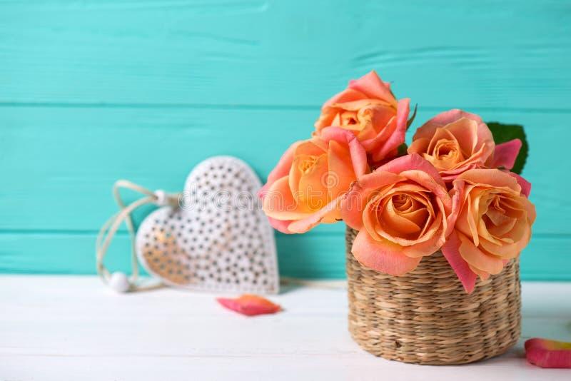 Свежие оранжевые розы и сердце на белой деревянной предпосылке против стоковые изображения