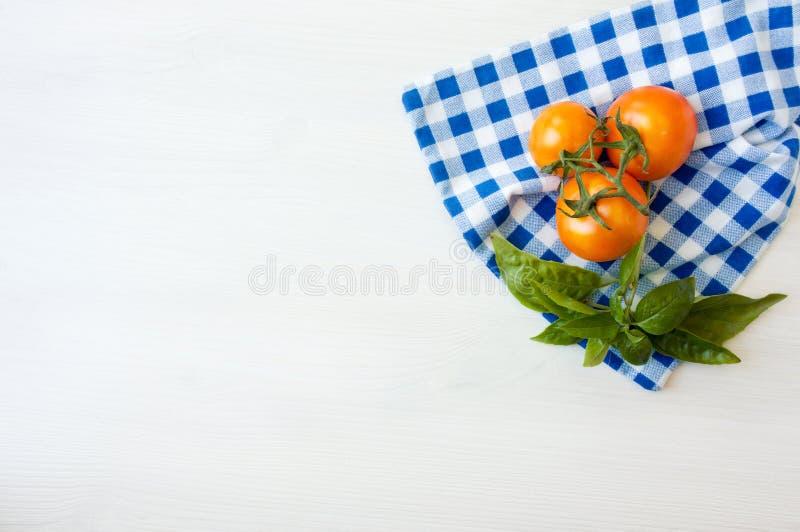 Свежие оранжевые томаты и базилик на деревянном столе стоковая фотография