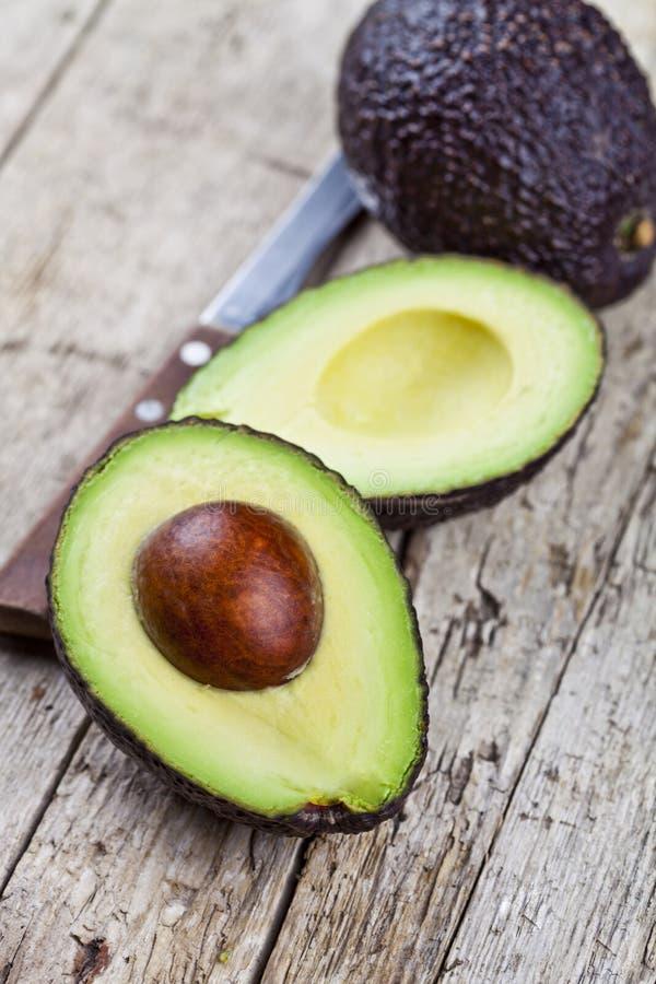 Свежие органические авокадо и нож на старой предпосылке деревянного стола Свежие половины авокадоа на деревенском деревянном back стоковая фотография rf