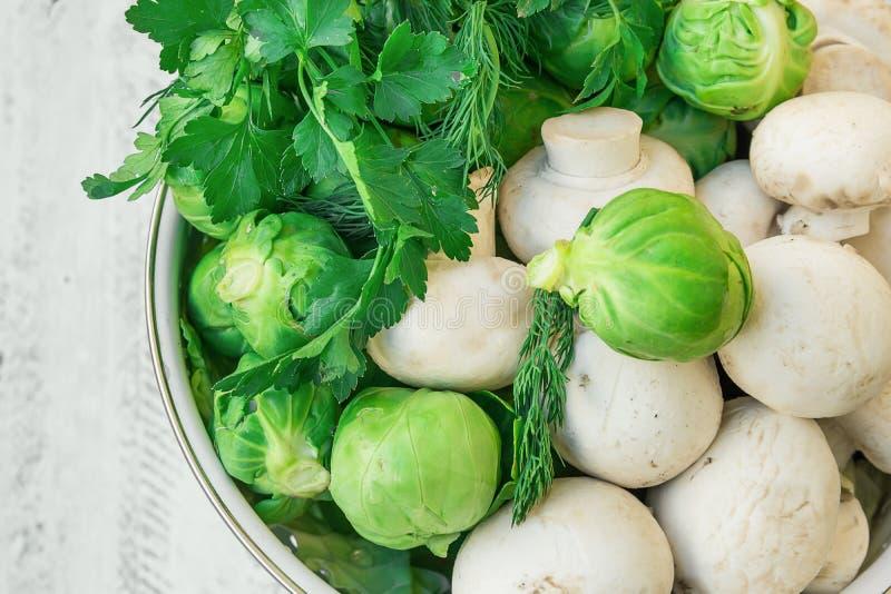 Свежие органические грибы укропа петрушки трав ростков Брюсселя овощей продукции зеленые в дуршлаге белого металла на деревянном  стоковая фотография