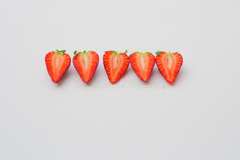 Свежие органические клубники уменьшанные вдвое и аранжированные в линии на белой предпосылке стоковое изображение