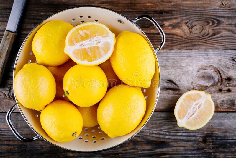 Свежие органические лимоны в дуршлаге на деревянной предпосылке Взгляд сверху стоковая фотография rf