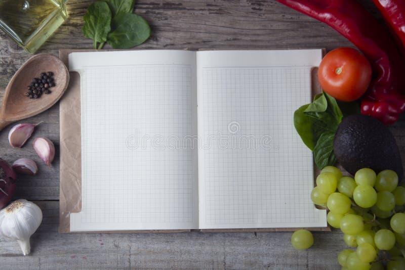 Свежие органические овощи, деревянная предпосылка и бумага для примечаний Раскройте предпосылку тетради и свежих овощей вокруг но стоковое фото rf