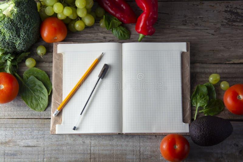 Свежие органические овощи, деревянная предпосылка и бумага для примечаний Раскройте предпосылку тетради и свежих овощей вокруг но стоковые изображения rf