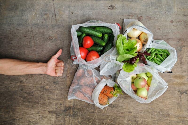 Свежие органические овощи, плоды и зеленые цвета в многоразовых сумках сетки и рука человека указывая ПОДОБИЕ знака, на деревянно стоковое изображение rf