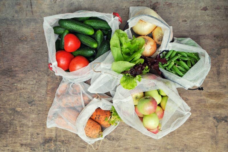 Свежие органические овощи, плоды и зеленые цвета в многоразовых повторно использованных сумках продукции сетки на деревянной пред стоковые фото