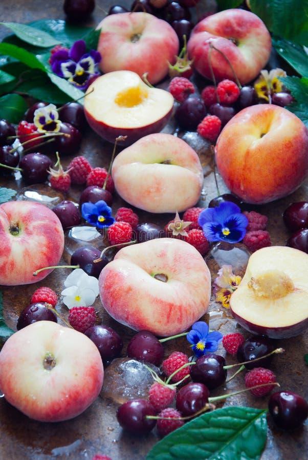 Свежие органические персики, поленики, вишни и цветки стоковое фото