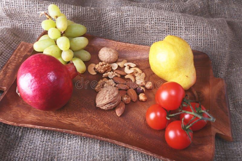 Свежие органические фрукты и овощи на деревянном подносе сервировки Сортированные яблоко, груша, виноградины, томаты и гайки стоковое изображение rf